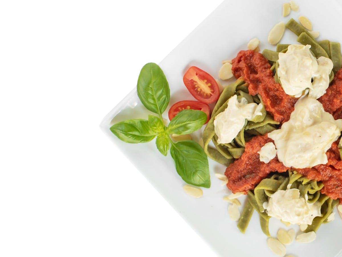 Tagliatelle w sosie pomidorowym przekładane pastą śmietanowąz kurczakiem i migdałami