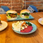 Przystawka: 🥗 Hummus z Kim Chi, podawane z chrupiąca tortillą , 🍔 Panoramiks - kotlet z ciecierzycy, kiszony pomidor, nachosy, sałata, cebula, guacamole, 🍰 Tofurnik z polewą czekoladową