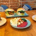 Przystawka: 🥗 Hummus z Kim Chi, podawane z chrupiąca tortillą , 🍔 Obeliks - placek ziemniaczany, tofu wędzone, sałata, cebula, ogórek, sos BBQ i czosnkowy, 🍰 Tofurnik z polewą czekoladową