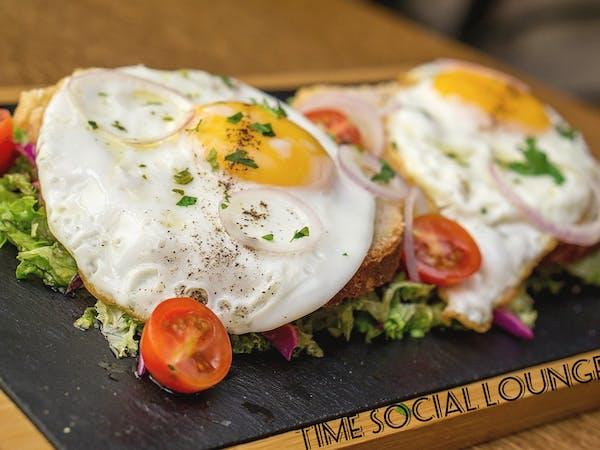 Ouă ochiuri pe pat de salată și pâine